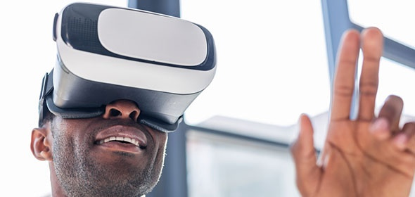 Man wearing VR goggles with 2 fingers on his left hand in the air as if he is interacting with something. Windows in the background.