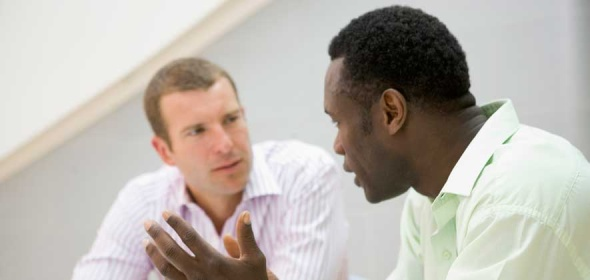 A man looking at another man while he discusses healthcare research consulting services for health workforce studies.