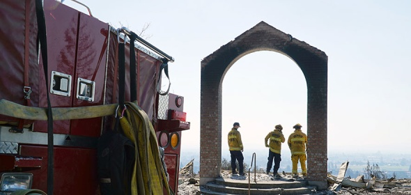 Fire fighters look out onto Santa Rosa, California after wildfires