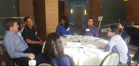 Physician leaders at a table discussing Healthforce Center's physician leadership development.