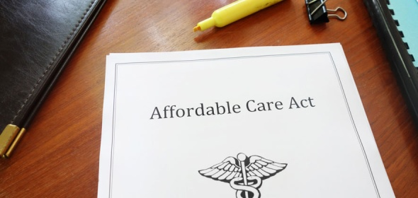 "A stack of documents with the top sheet that reads: ""Affordable Care Act""."