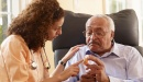 Home health aide caregiver works with older adult