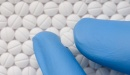 Background of round white pills with an indented line through the center. From the bottom right of the image a thumb and index finger in blue latex gloves extend holding another white pill with an indented line through the middle.